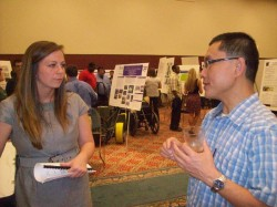Dr. Wei Tu talking to a student in COUR Undergraduate Research Symposium